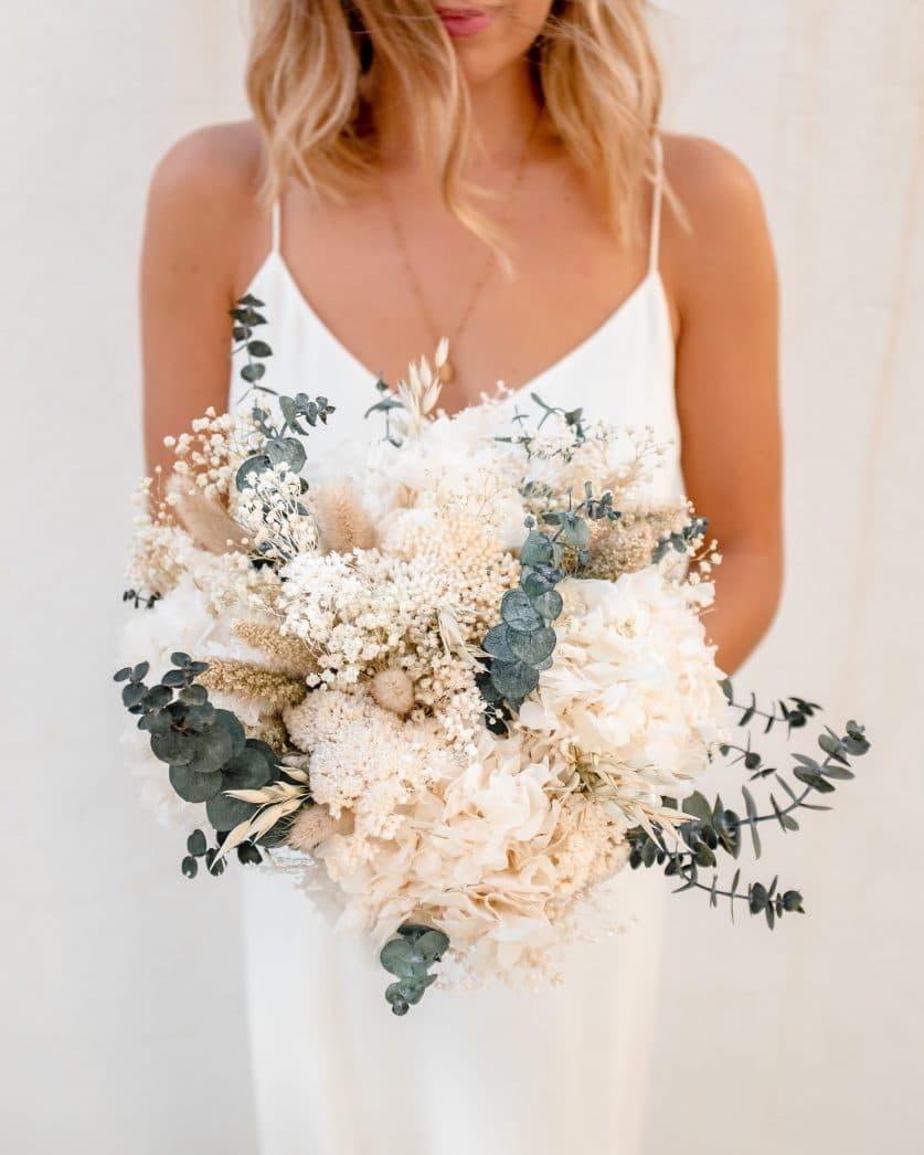 femme blonde en robe de mariée qui tient un bouquet de fleurs séchées rosa cadaqués hortensia eucalyptus