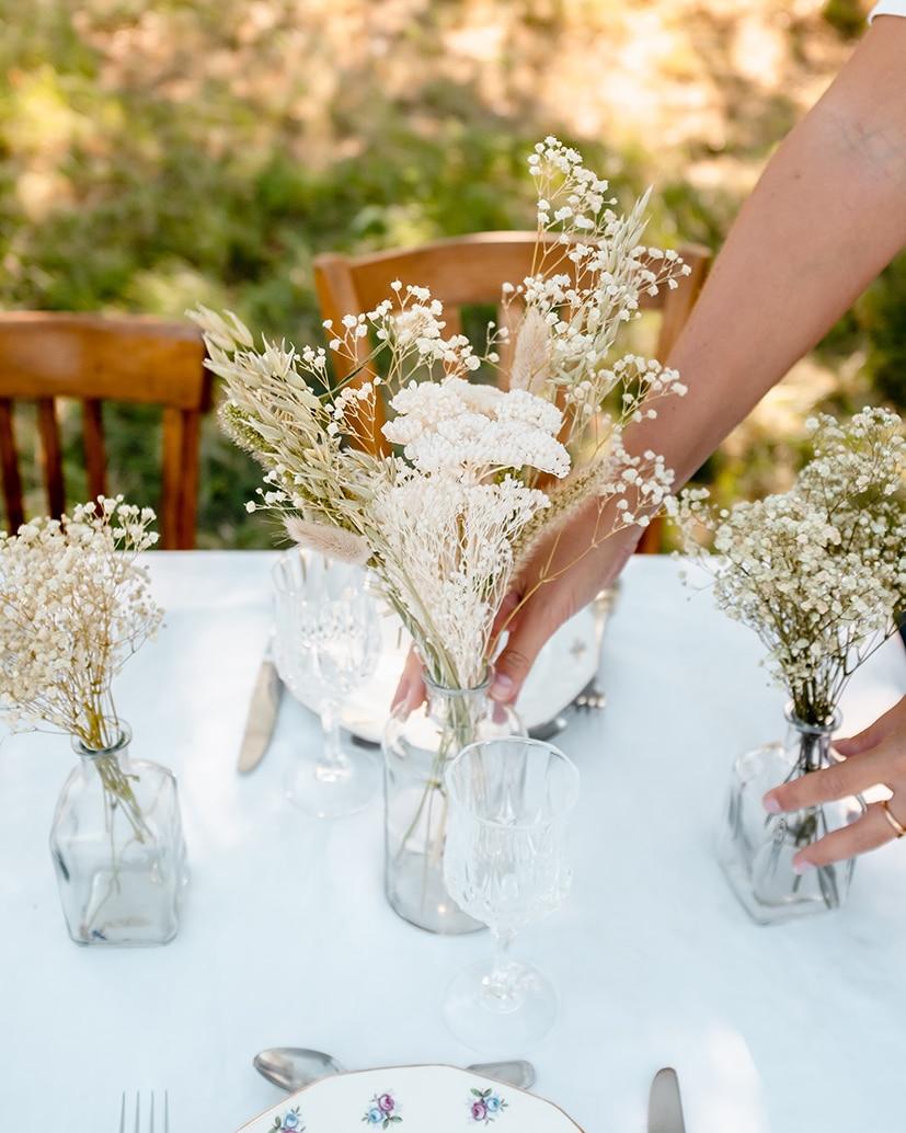 Personne qui pose un centre de table en fleurs séchées Rosa Cadaqués