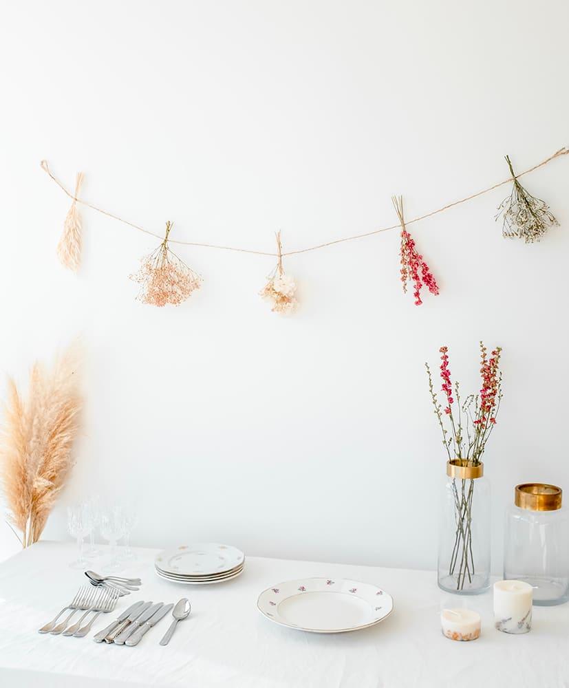 Guirlande en fleurs séchées disposée contre un mur
