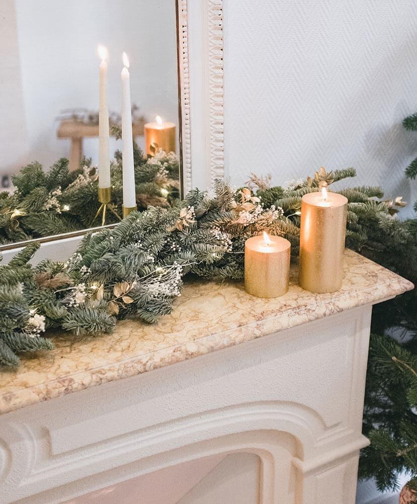 Guirlande de fleurs séchées sapin posée sur une cheminée surmontée d'un miroir ambiance tamisée