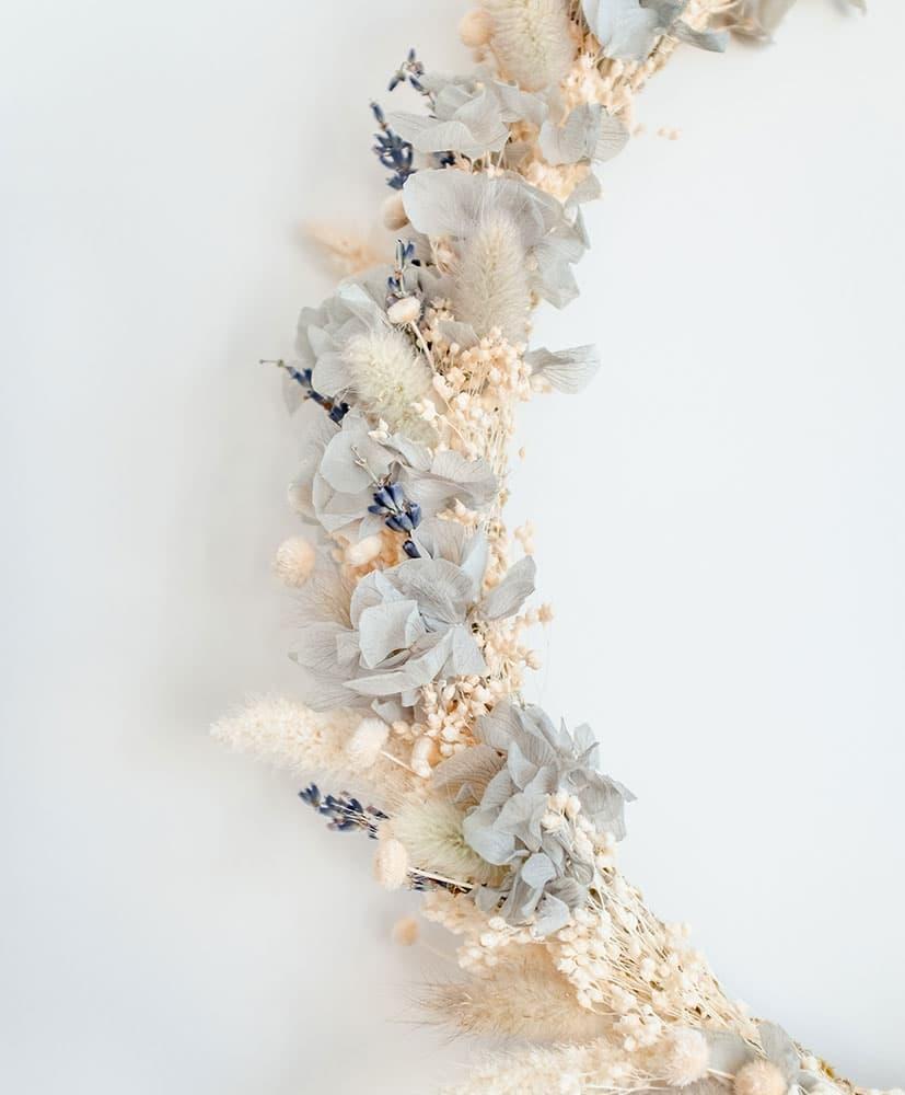 couronne de fleurs séchées accrochée au mur dans les tons bleu-gris avec de l'hortensia bleu clair pour décorer les chambres d'enfants