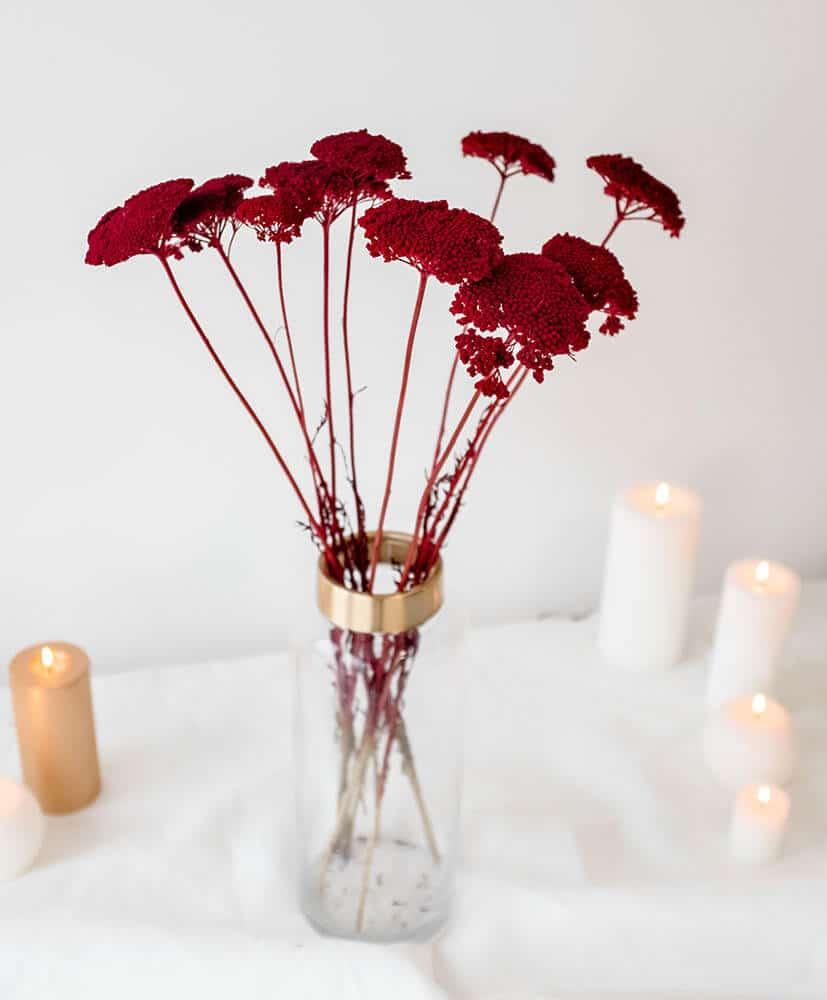 Botte d'achillées rouges dans un vase transparent, posé sur une table avec une nappe blanche et des bougies allumées en fond