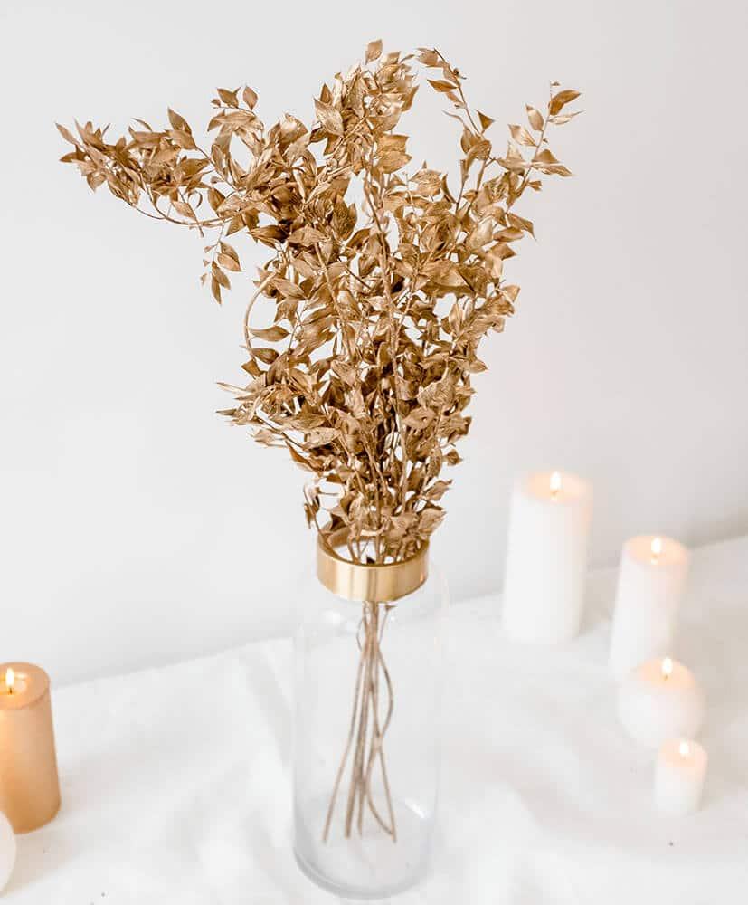 Botte de Ruscus Or disposée dans un vase posé sur une table blanche