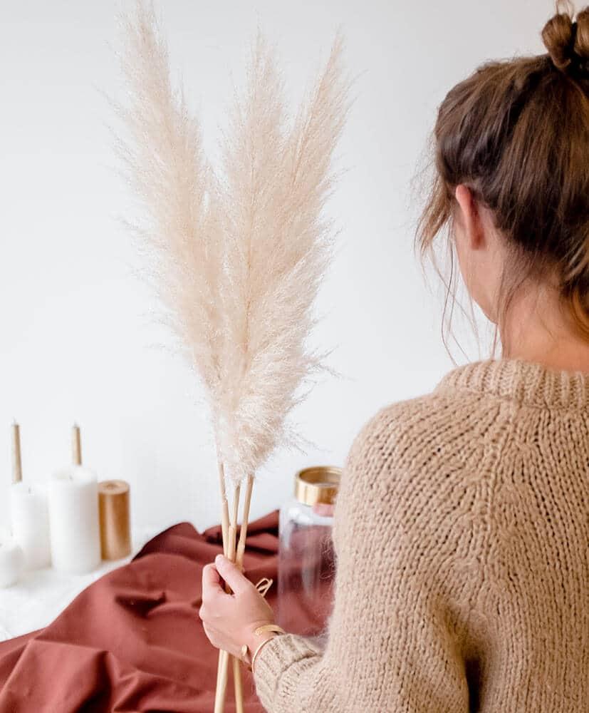 herbes de pampa tenues dans une main, la personne est de dos et porte les herbes de pampa
