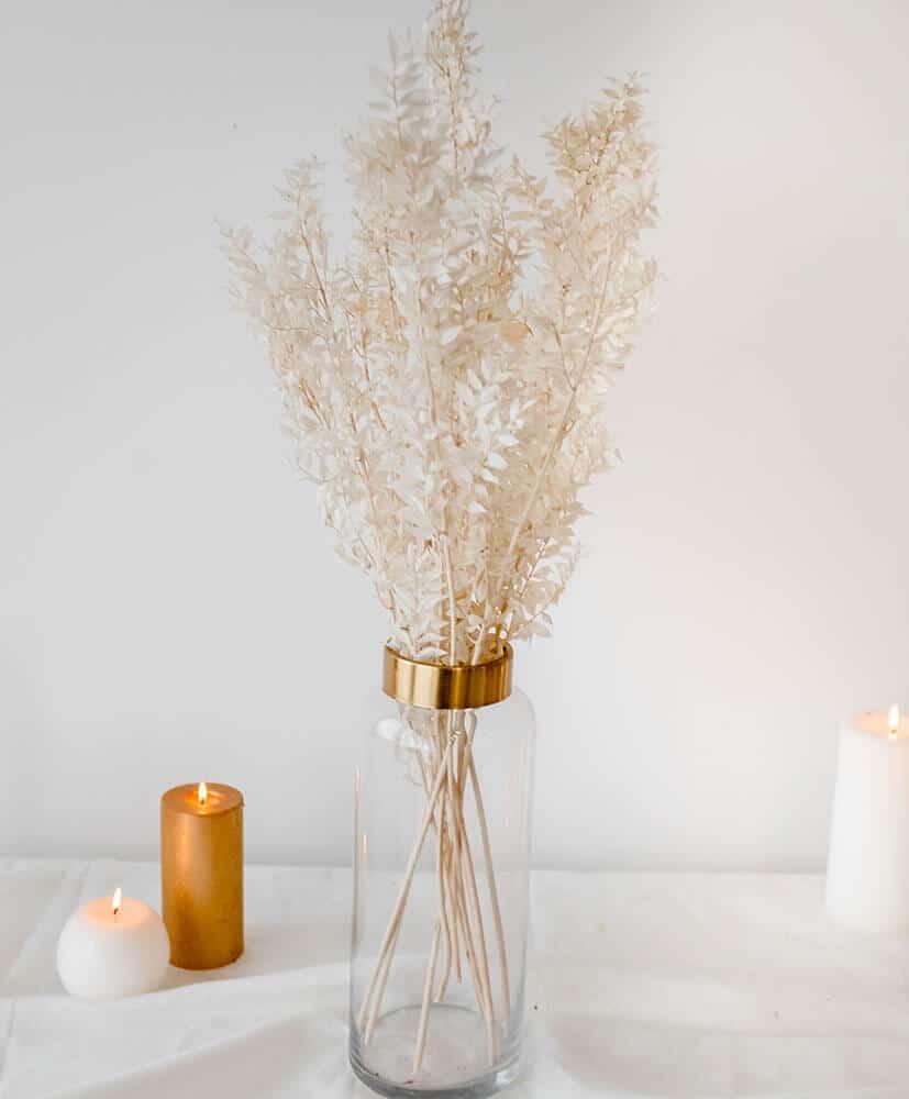 Botte de russes blanc dans un vase transparent posé sur une table avec des bougies en fond, esprit de Noël