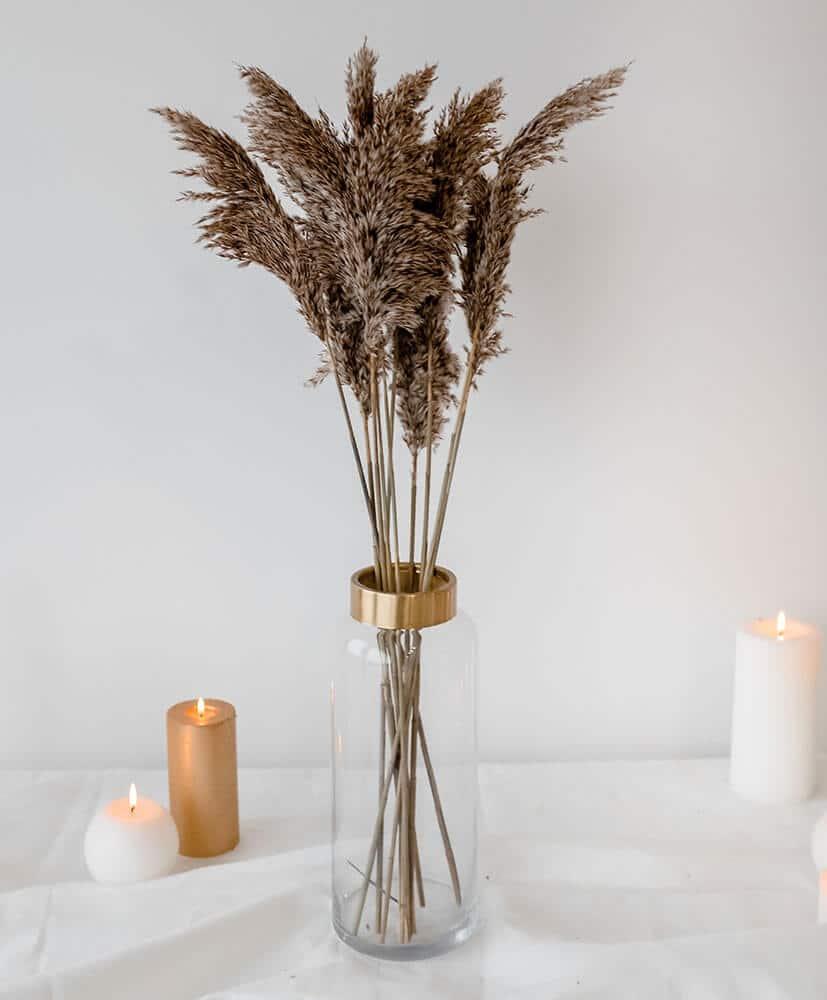 Botte de Siergras, une herbe de Pampa, dans un vase transparent posé sur une table avec nappe blanches et bougies en fond