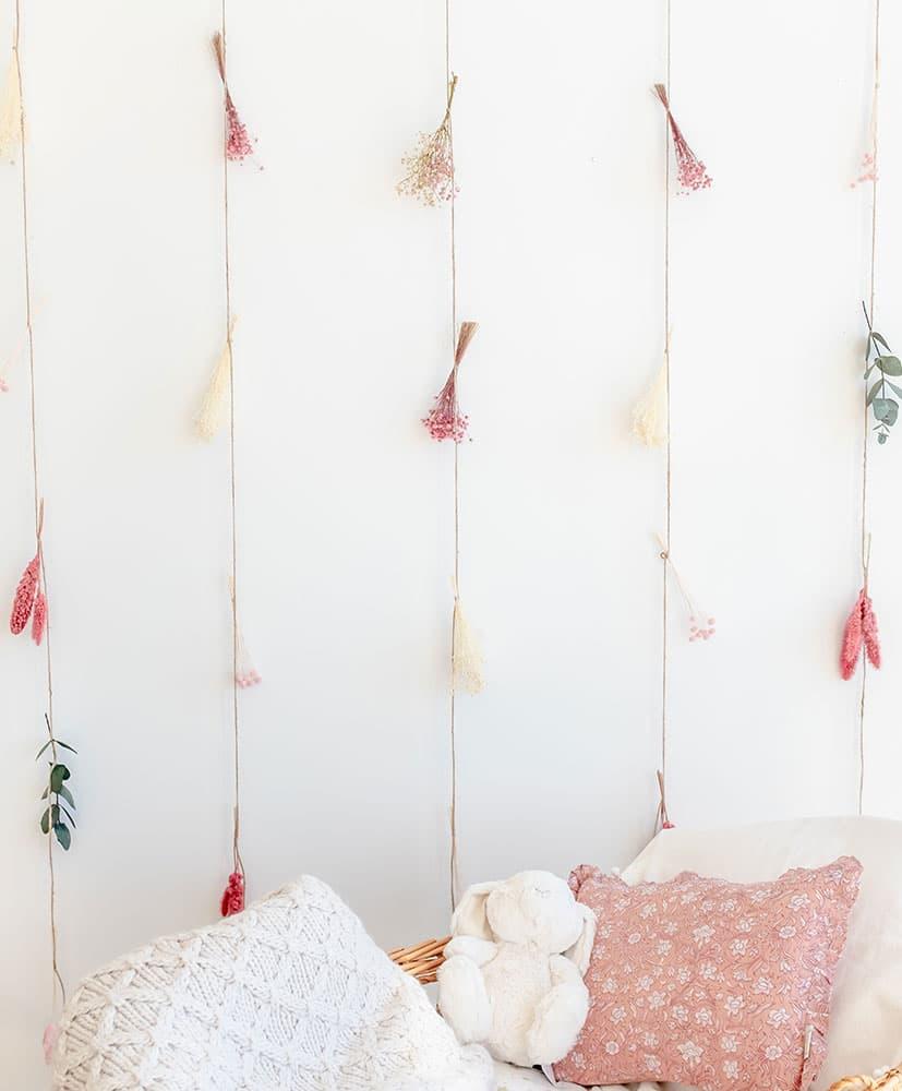 rideau de fleurs séchées dans les tons roses utilisé en tête de lit pour les enfants