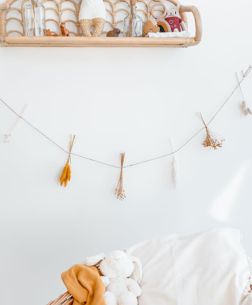 Guirlande de fleurs séchées dans les tons moutarde accrochée en tête d élit pour décoration chambre d'enfants